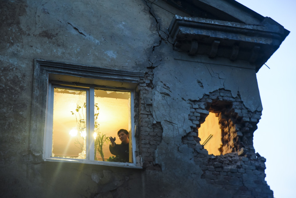 Residents observe damage in their flat after shelling between Russia-backed separatists and Ukrainian government troops in Donetsk, Eastern Ukraine, Monday.