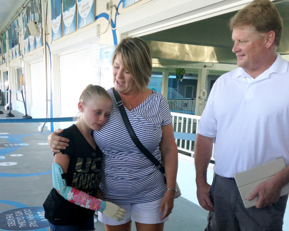 Annika Emmert, left, a 10-year-old who was born without part her right arm, wears her new arm as she stands with her parents.