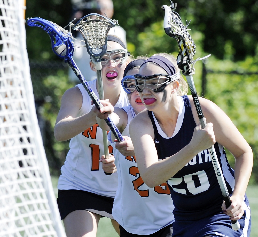 Shannon Fallon of Yarmouth takes the ball to the net for a goal while eluding the North Yarmouth Academy defense during their schoolgirl lacrosse regular-season finale Thursday. Yarmouth earned a 15-3 victory.