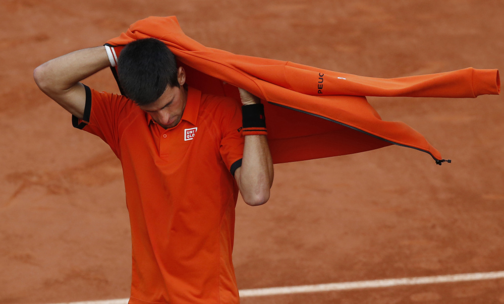 Serbia's Novak Djokovic puts on his jacket after imminent thunderstorms forced officials to interrupt the semifinal match of the French Open tennis tournament against Britain's Andy Murray at the Roland Garros stadium in Paris, France, on Friday.