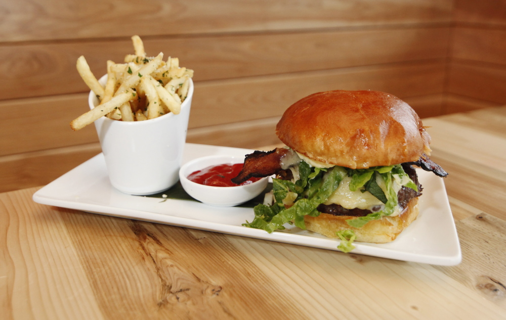 The Rudy's Burger is topped with bacon, cheddar, caramelized onion, shredded lettuce and horseradish aioli.