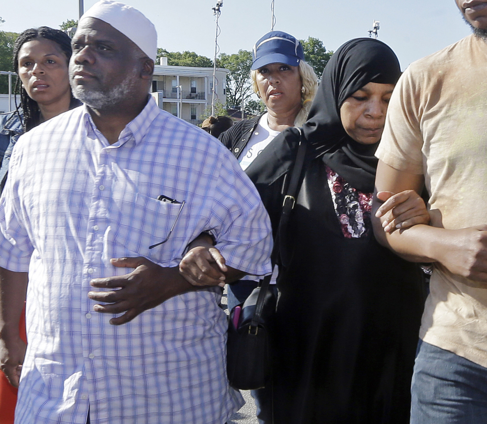 Rahimah Rahim, middle, and Ibrahim Rahim, left, the mother and brother of Usaama Rahim, walk away after a news conference Thursday in Boston's Roslindale neighborhood where Usaama Rahim was shot to death by police.
