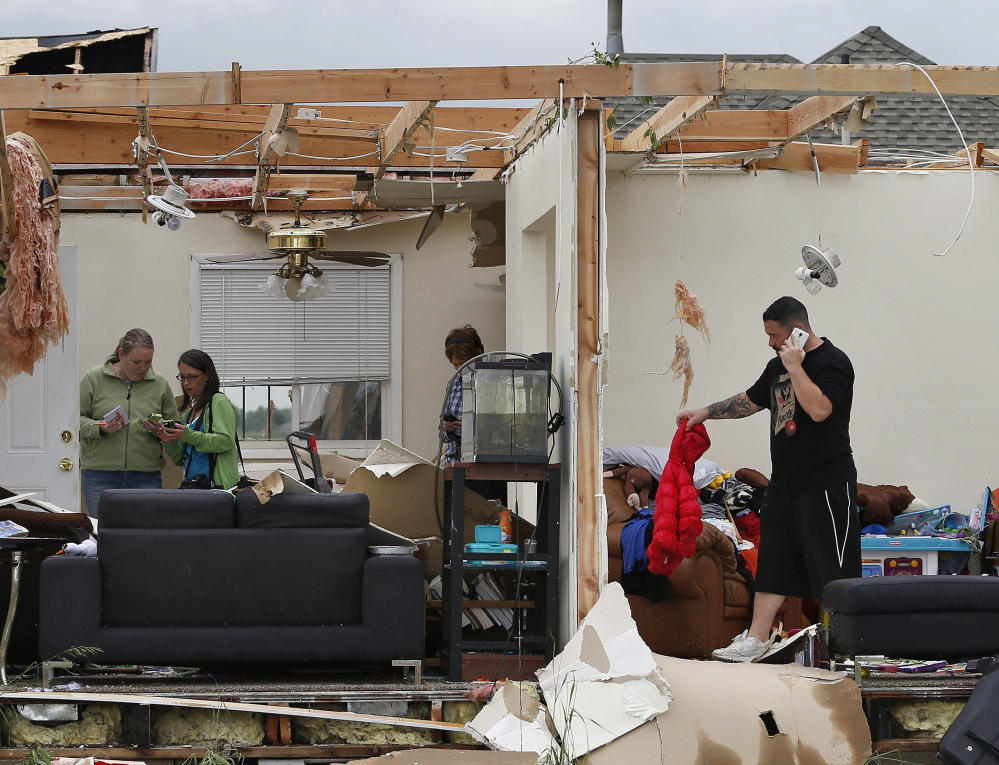 Brandon Scott salvages items from his half-gutted home after he and his family spent the night in the basement near the town of Berthoud, Colo., on Friday.