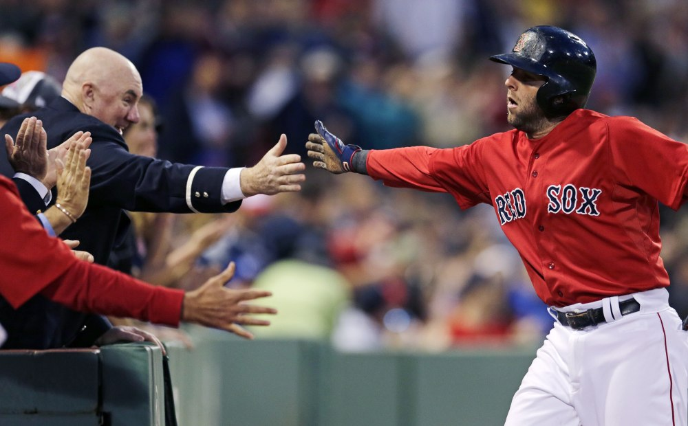 Boston's Dustin Pedroia is congratulated by fans after scoring on a single by Brock Holt in the fifth inning Friday night against the Oakland Athletics. Pedroia had three hits in the game.