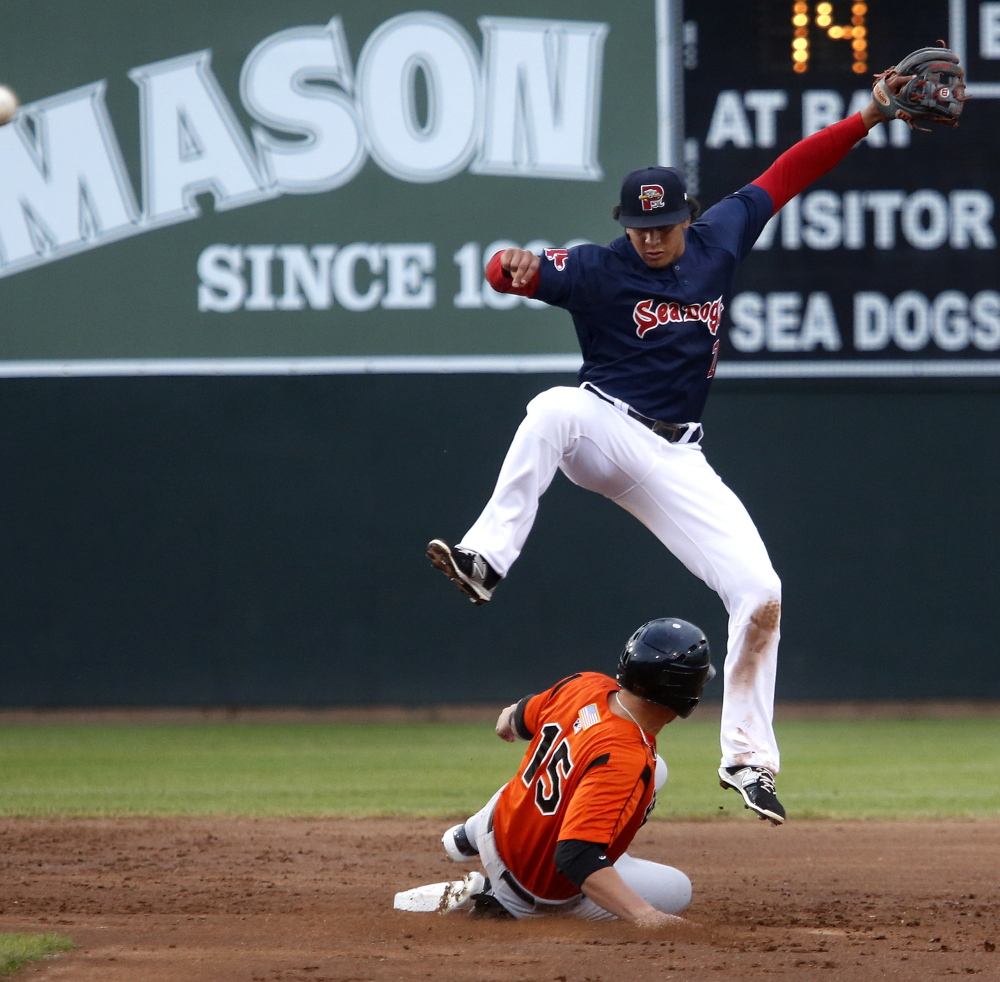 Sea Dogs shortstop Marco Hernandez leaps over Brandon Snyder of Bowie after making a throw to first to complete a double play Friday night.