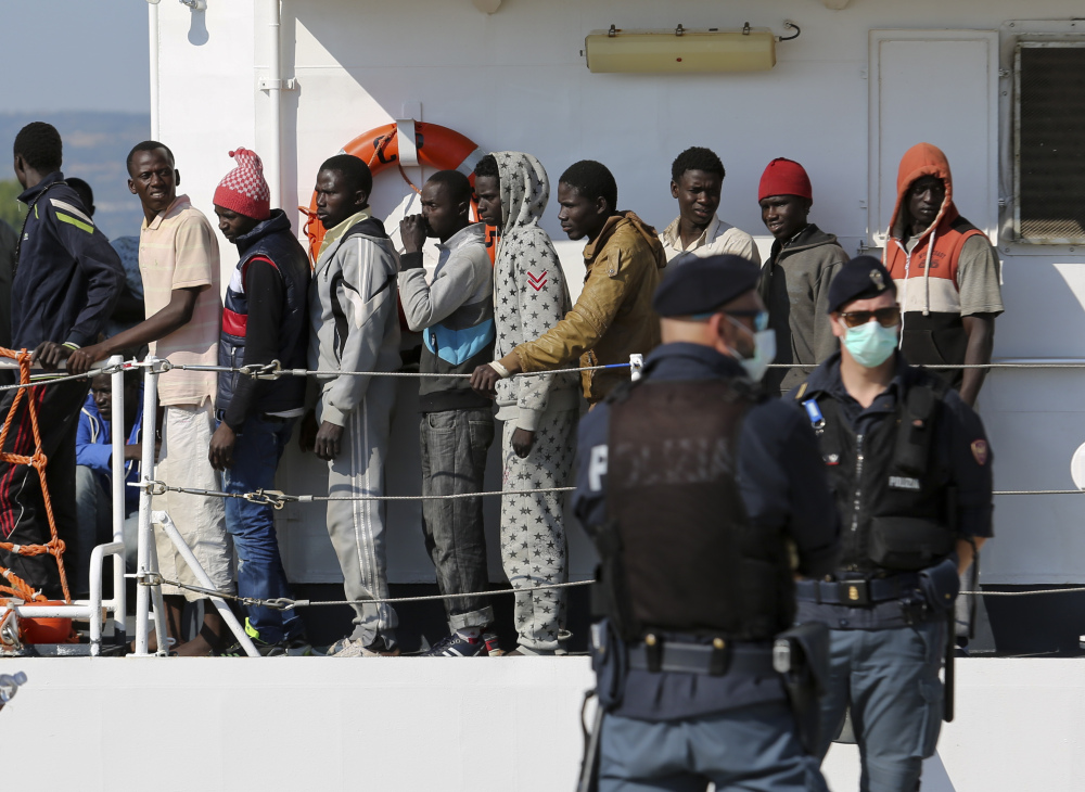 Migrants disembark from the Italian Coast Guard vessel Peluso as they arrive in the Sicilian port town of Augusta on Wednesday.