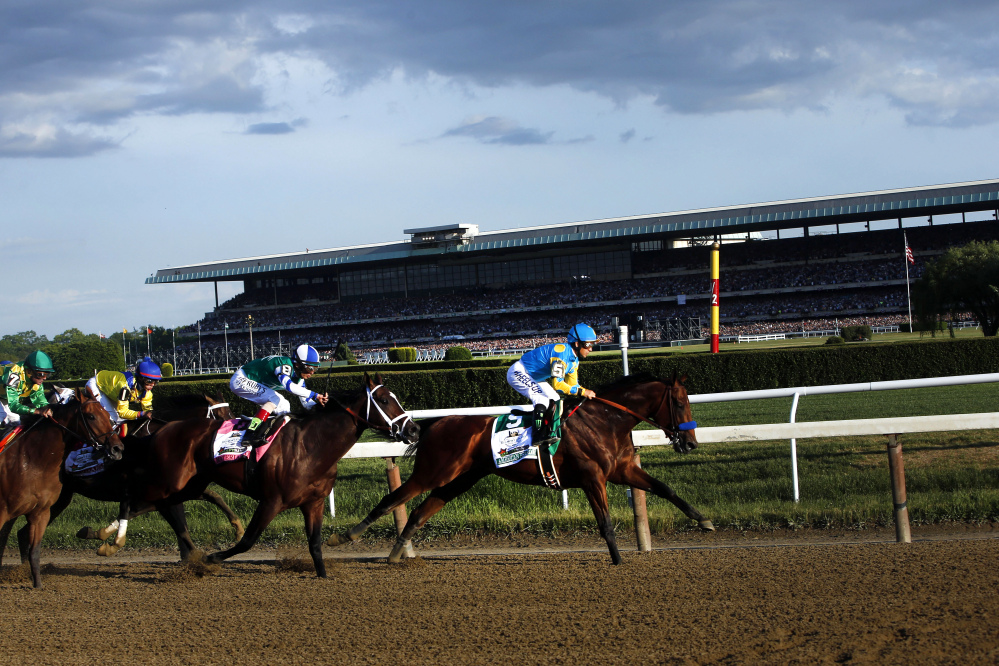 American Pharoah (5) leads the field entering turn three on the way to a Triple Crown victory during the 147th running of the Belmont Stakes at Belmont Park on Saturday in Elmont, N.Y.