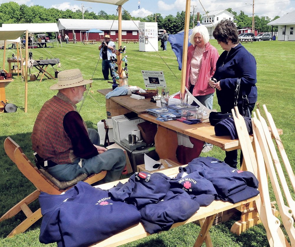Gary Moore speaks with Sue McLaughlin, center, and Jill Low at a Civil War store set up Saturday during a reenactment in Clinton.