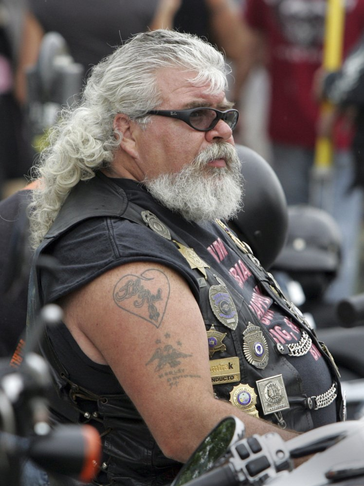 Mark Gauthier of Gilford watches the scene at Weirs Beach wearing a variety of police badges on his vest, during bike week in Laconia, N.H., in 2010.
