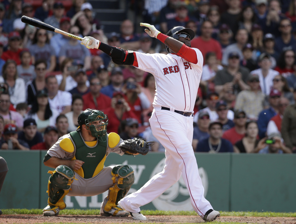 Boston Red Sox designated hitter David Ortiz hits a sacrifice fly, allowing Brock Holt to score in the eighth inning against Oakland Sunday in Boston.
