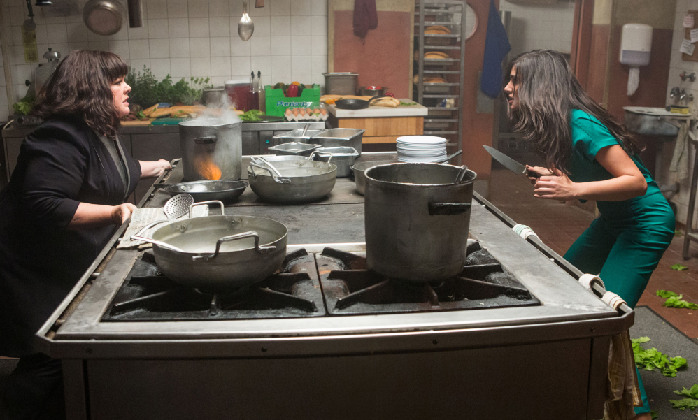 "Melissa McCarthy, left, faces off against a knife-wielding adversary, Nargis Fakhri, in a scene from ""Spy."""