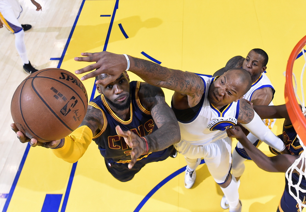 Cleveland's LeBron James goes up for a shot against Marreese Speights of the Golden State Warriors during Game 2 of the NBA finals Sunday in Oakland, Calif. James scored 39 points, and the Cavaliers tied the series with a 95-93 overtime win.