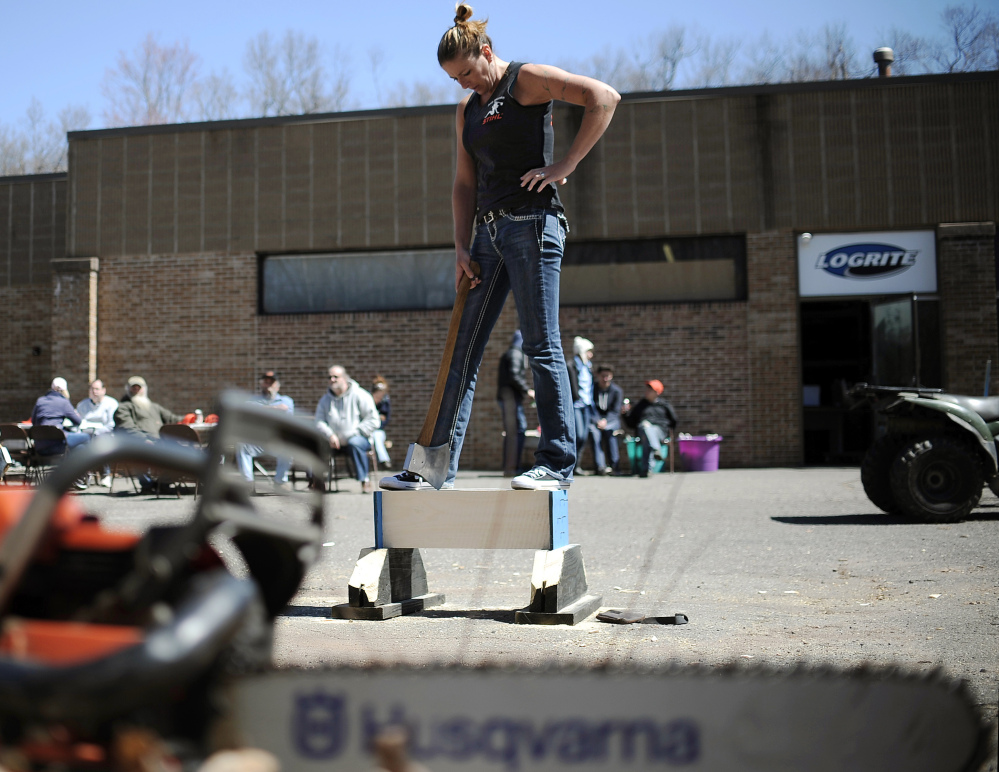 In this Saturday, April 25, 2015 photo, Alissa Harper, founder of Axe Women of Maine, pauses before chopping a block of wood during a demonstration in Vernon, Conn. Harper, of Bar Harbor, Maine, started Axe Women in 2010. Group members hold six world titles in various women lumberjack competitions.