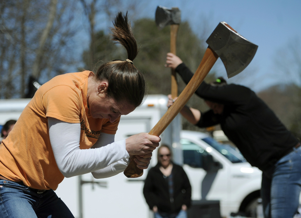 In this Saturday, April 25, 2015 photo, Alissa Harper, left, and Michele Watkins chop blocks of wood during the Axe Women of Maine's demonstration in Vernon, Conn.