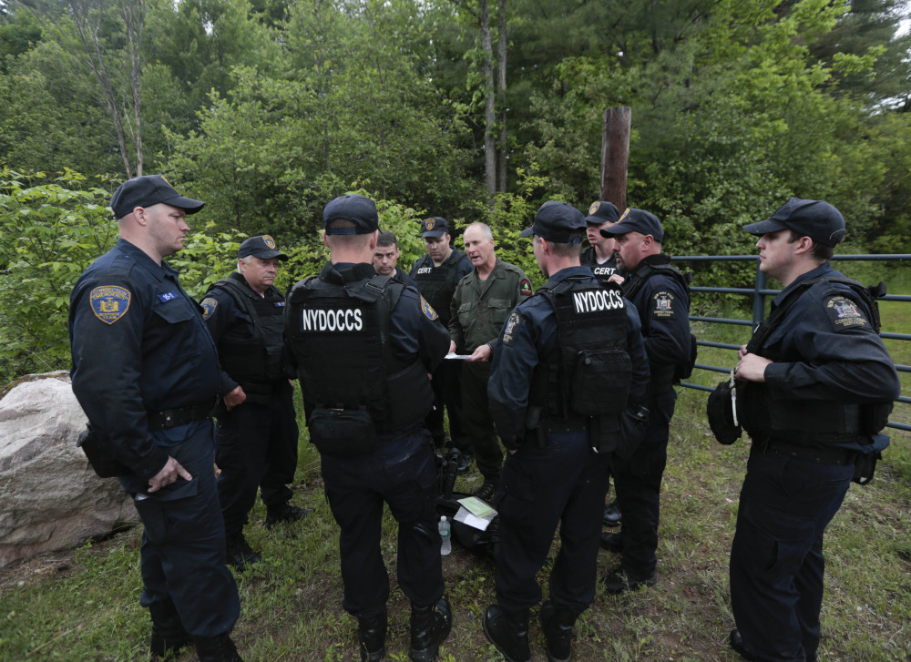State forest ranger Dan Fox reviews a map with members of the New York State Department of Corrections and Community Supervision emergency response team before entering a wooded area in search of two prisoners who escaped from the Clinton Correctional Facility on Monday in Dannemora, N.Y.