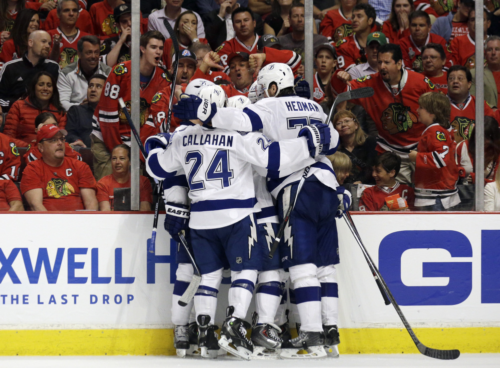 Teammates congratulate Tampa Bay's Cedric Paquette on his tie-breaking goal against the Chicago Blackhawks late in the third period Monday night.