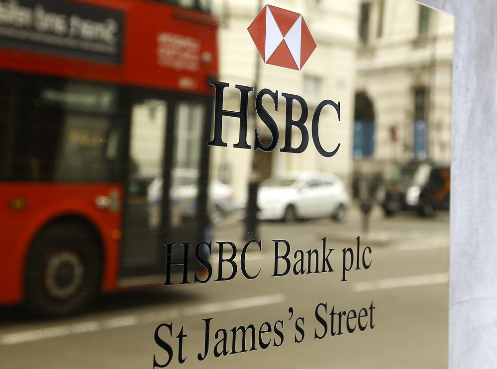 A London bus is reflected as it drives past an HSBC plaque in St James's Street in London, Tuesday, June 9, 2015.