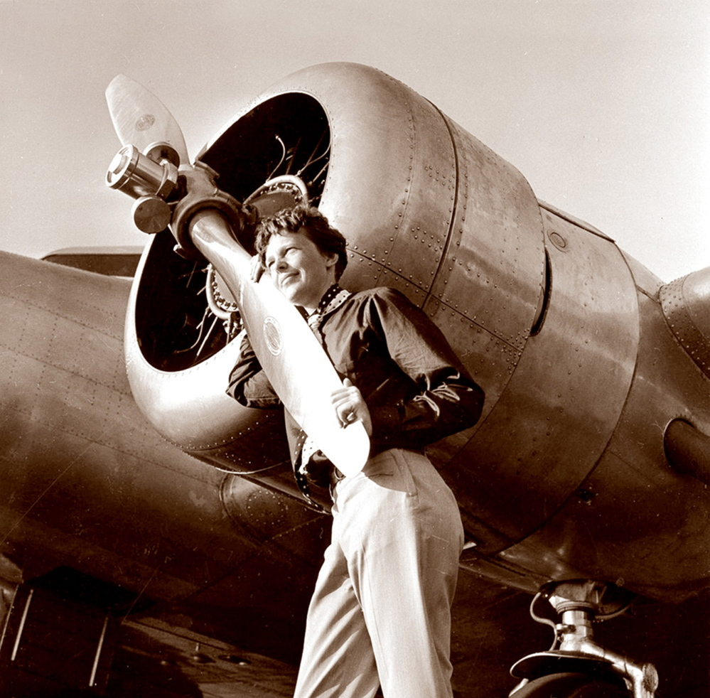 In this May 20, 1937 photo, aviator Amelia Earhart poses next to her Electra plane's propeller. The photo was taken by Albert Bresnik at Burbank Airport in Burbank, Calif. It was a clear spring day in 1937 when Earhart, ready to make history by flying around the world, brought her personal photographer to the airport to document the journey's beginning.