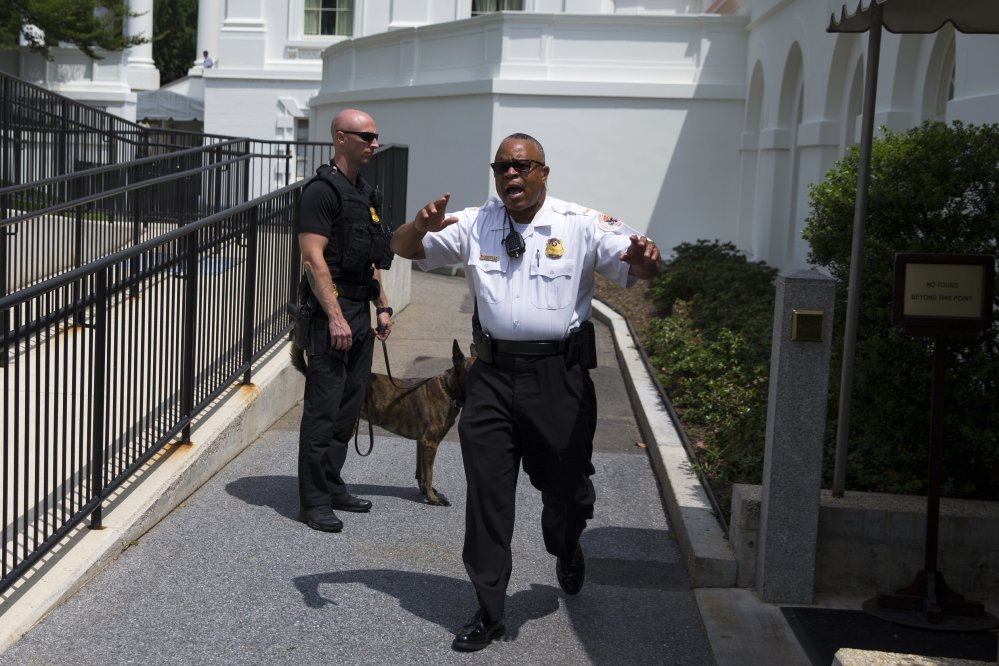 Secret Service police move members of the media outside the briefing room as they evacuate parts of the White House in Washington on Tuesday.