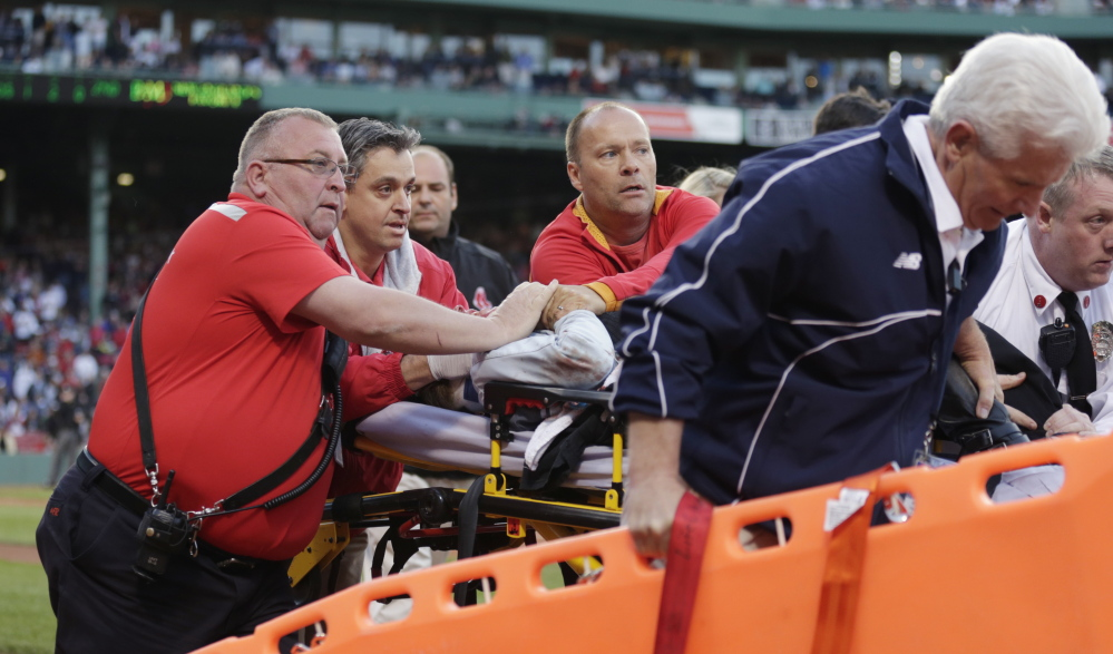 Boston Red Sox medical personnel tend to a woman, who was hit by a wooden shard off a broken bat of Oakland Athletics' Brett Lawrie, at Fenway Park in Boston on Friday.