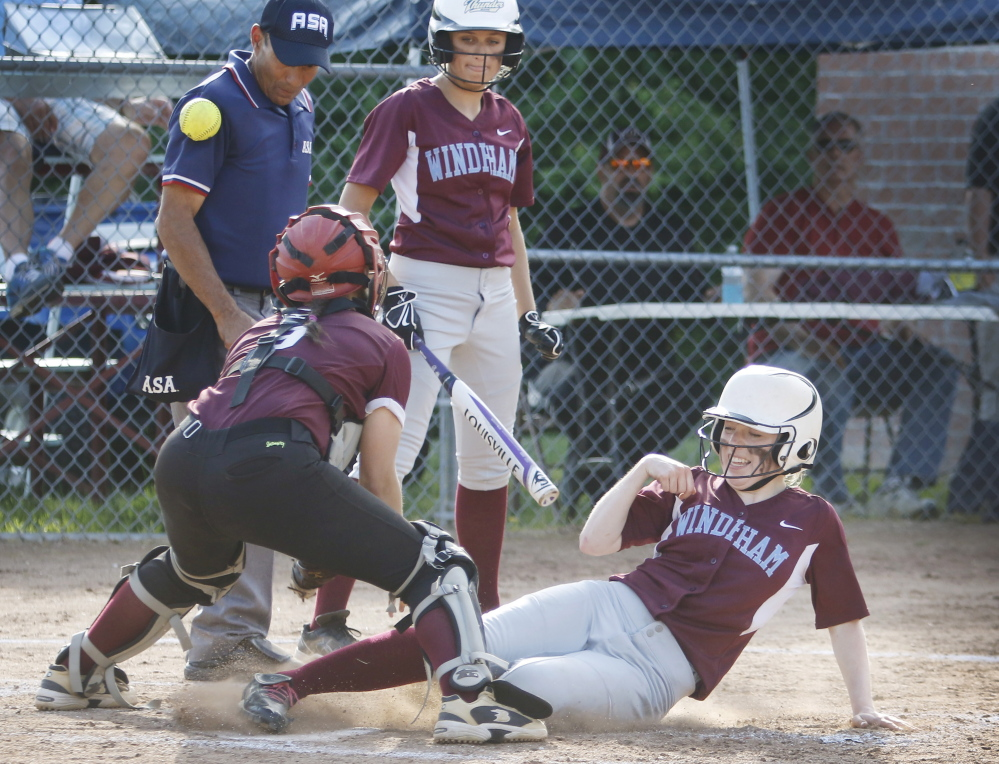 June 9: Windham batter Lauren Talbot watches as Katie Hunter slides into home to score as Gorham catcher Noelle Dibiase just misses the throw in the sixth inning at Windham Tuesday. Jill Brady/Staff Photographer