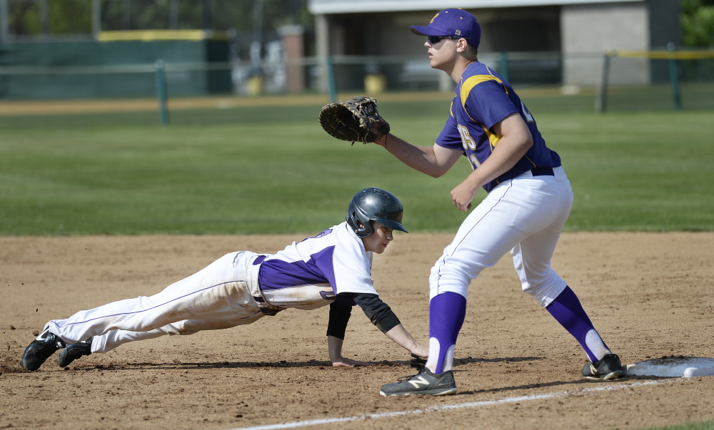 June 9: Kevin Goldberg of Deering dives back to first on a pickoff attempt as Jared Brooks of Cheverus waits for the throw in Tuesday's Western Class A baseball prelim. Deering won, 12-2.