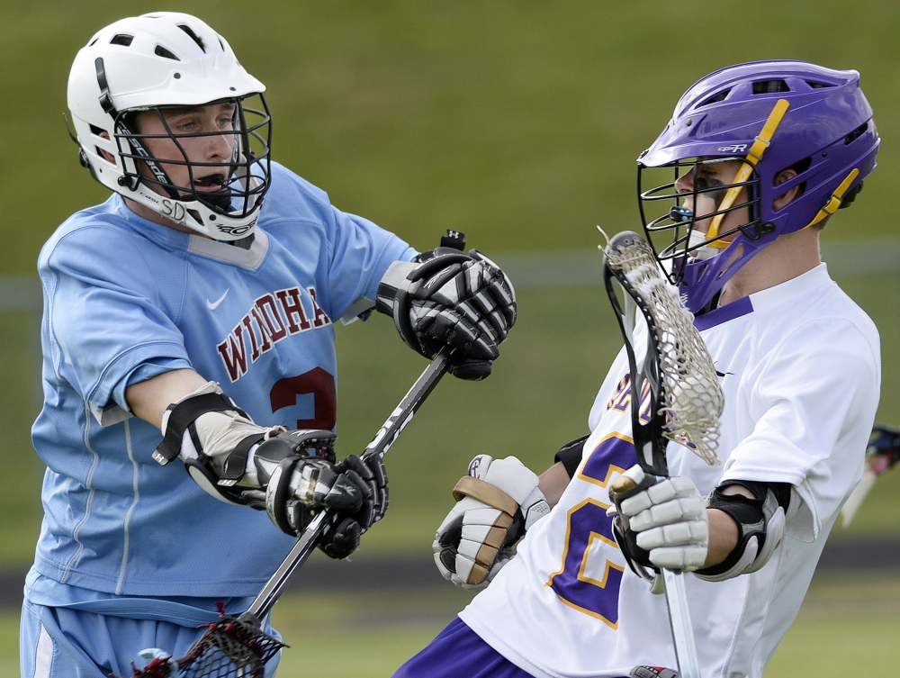 Max Coffin of Cheverus, right, tries to elude Jason Nielsen of Windham during Wednesday's game.