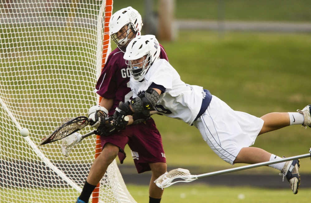 Grayson Post of Westbrook makes a diving but unsuccessful bid for a goal Wednesday night as Gorham goalie Carter Landry, who made 11 saves in a 12-11 victory, stands his ground.