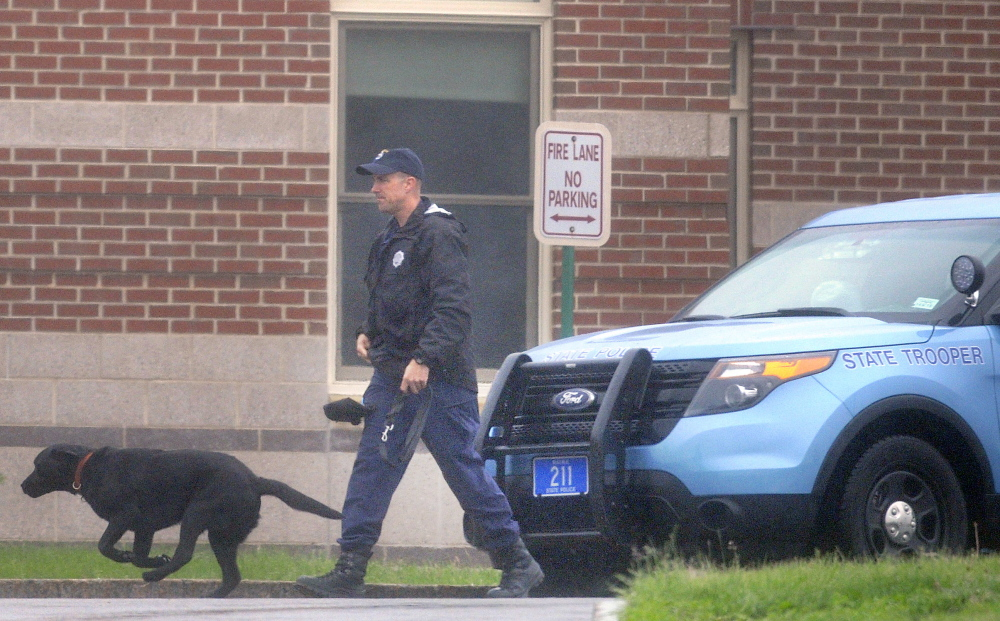 A state trooper escorts a police dog June 2 around the exterior of Cony High School in Augusta after an evacuation because of a bomb threat. Since then, two more threats have been reported.