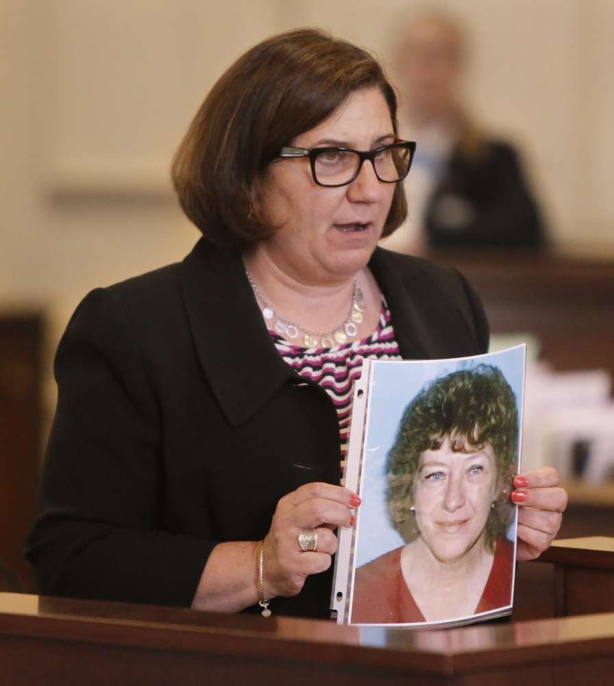 Assistant Attorney General Leane Zainea holds a photo of Patricia Noel, the victim, during opening statements in the murder trial of Derek Poulin at York County Superior Court in Alfred on Thursday.