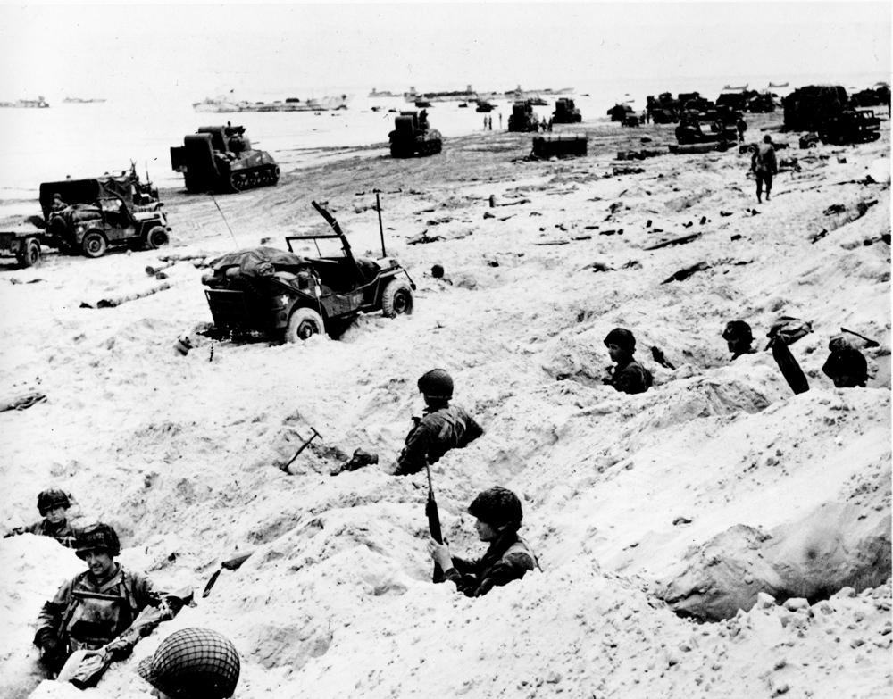 American soldiers of the Allied Expeditionary Force secure a beachhead during initial D-Day landing operations at Normandy, France, on June 6, 1944.