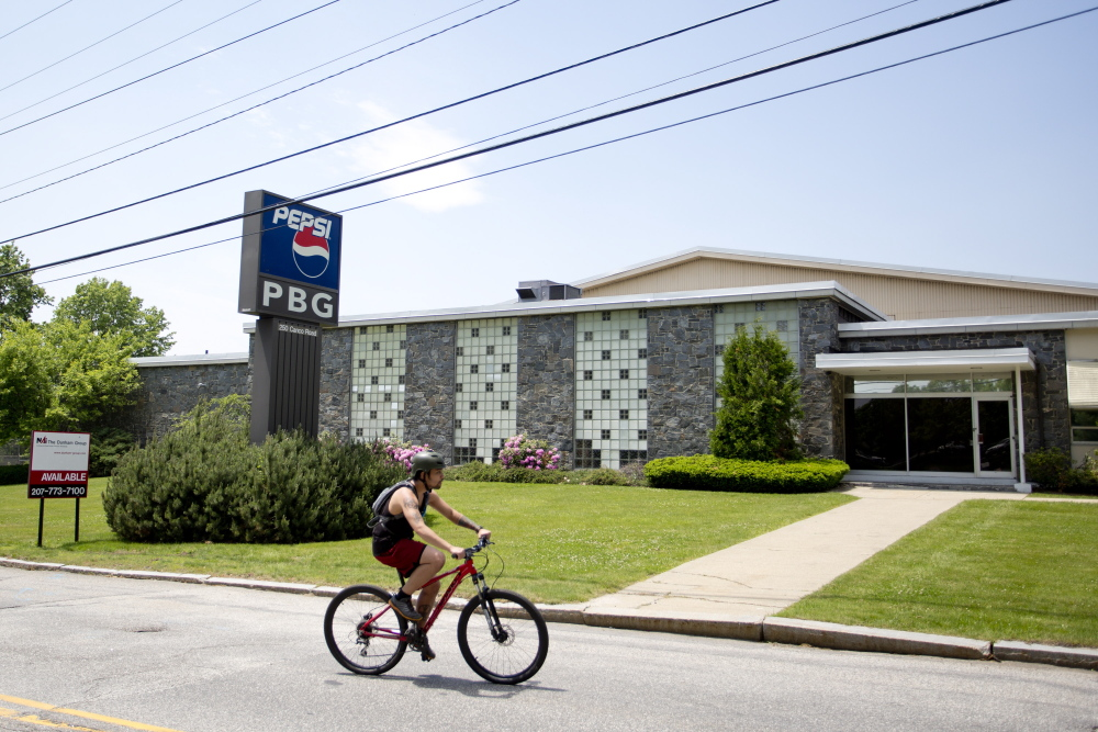 A bicyclist passes the former Pepsi building at 250 Canco Road on Thursday. The building is the proposed new site of Portland's public works department, but will require voters' approval.