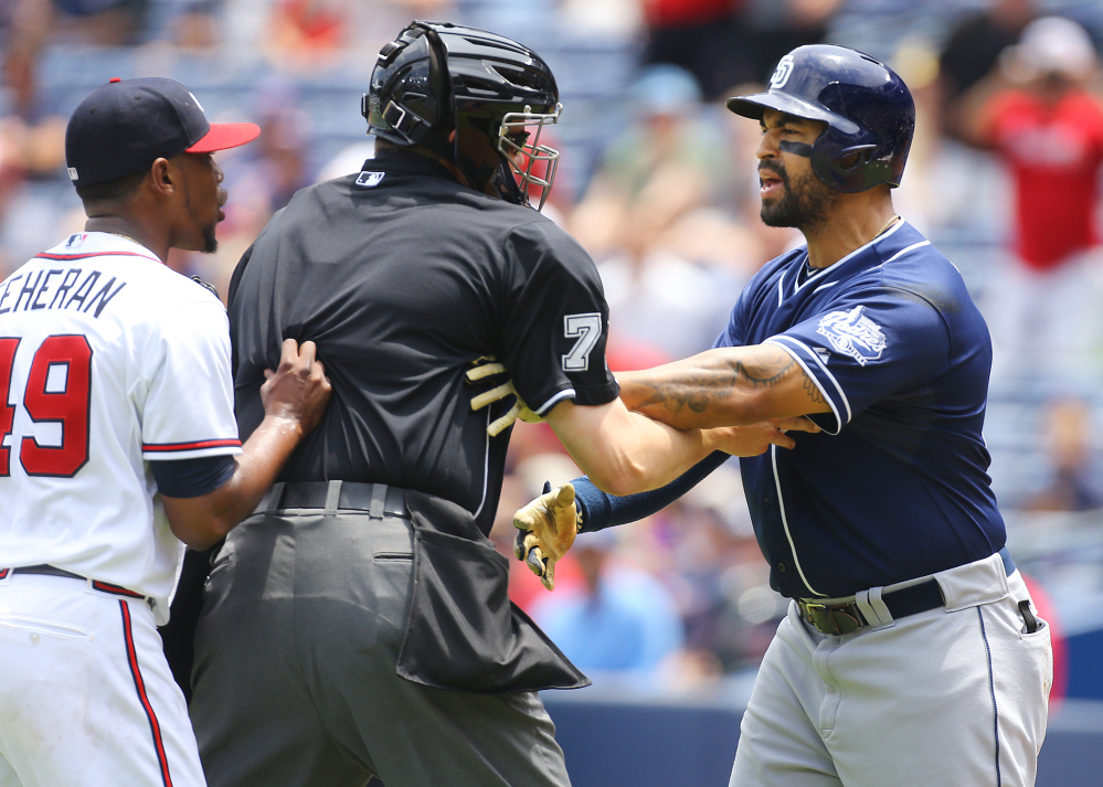 Home plate umpire Jordan Baker separates Atlanta's Julio Teheran, left, and San Diego's Matt Kemp after Teheran hit Kemp with a pitch in the first inning of the Padres' 6-4 win Thursday.