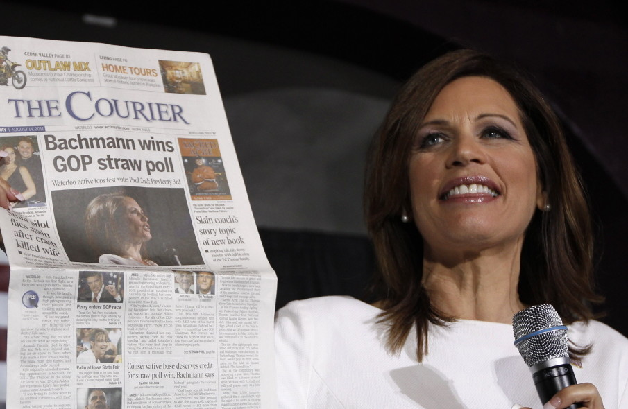 Republican presidential candidate Rep. Michele Bachmann, R-Minn., holds up a newspaper saying that she won the Iowa Republican straw poll in 2011.