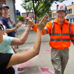 Ray Shevenell, 74, gets high-fives from supporters as he completes his 188-mile walk Friday. He retraced the steps from Quebec to Biddeford that his great-great-grandfather, Israel Shevenell, made in search of work in 1845.