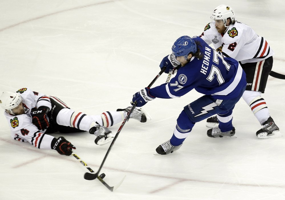 Chicago Blackhawks defensemen Niklas Hjalmarsson, left, and Duncan Keith break up a scoring opportunity by Tampa Bay's Victor Hedman. Goals by either team have been a rarity in this tightly played championship series.