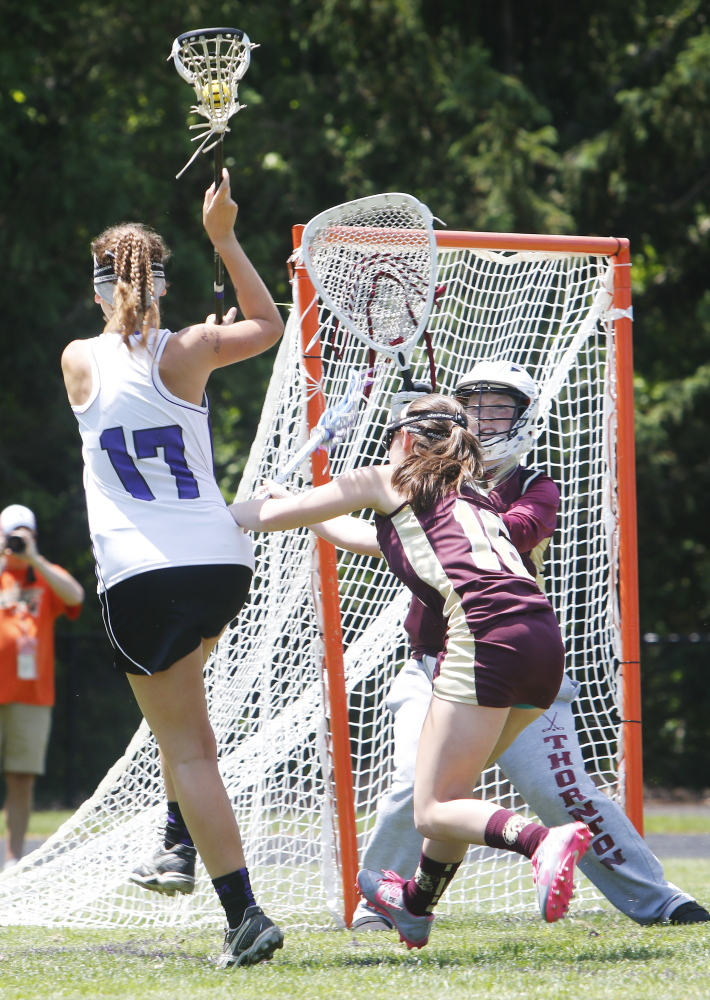Thornton Academy goalie Allie Spinney waits for a shot by Lindsey Poirier of Marshwood as Kailey Dubuque defends.
