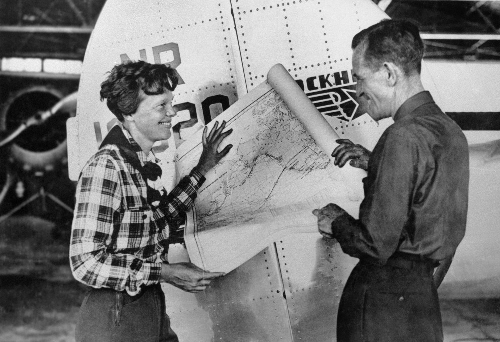 Aviator Amelia Earhart, left, and navigator Fred Noonan pose with a map of the Pacific Ocean showing the planned route of the round-the-world flight during which they and their plane went missing.
