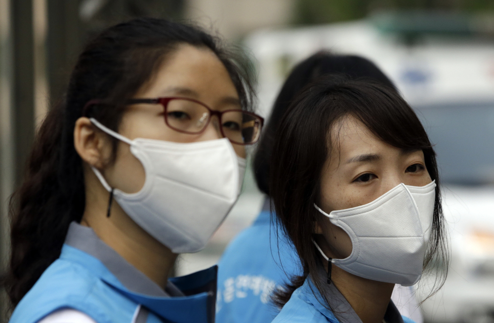 South Korean health workers take precautions against Middle East respiratory syndrome. So far, the virus in South Korea has killed 14 people and spread only in hospitals.