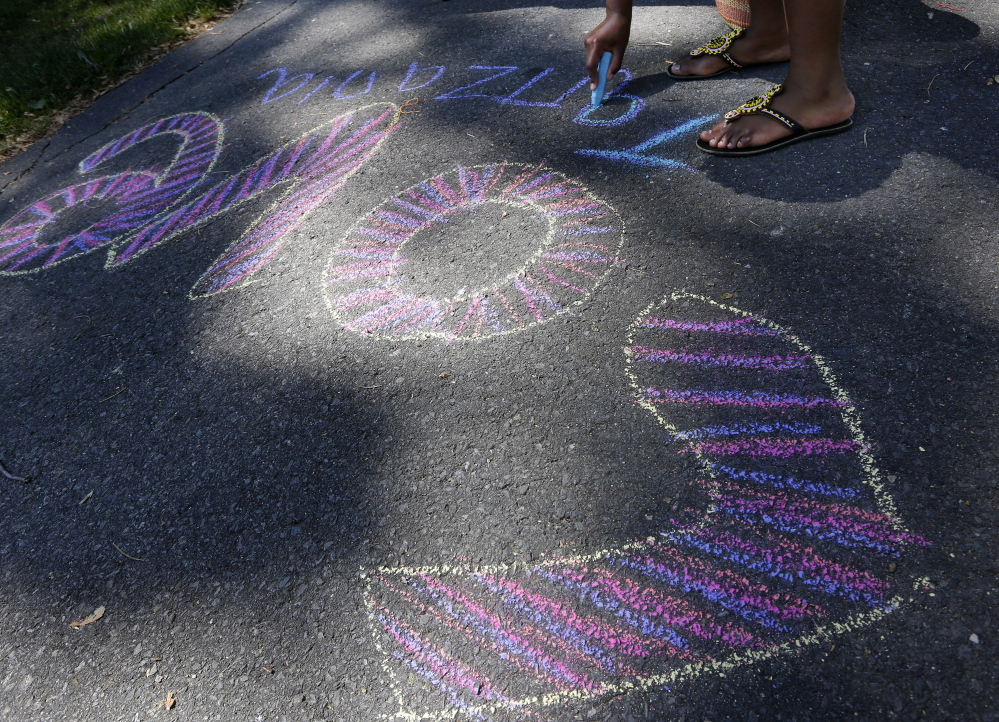 Deborah Mrema, 18, of Portland, originally from Tanzania, draws with chalk on the sidewalk.