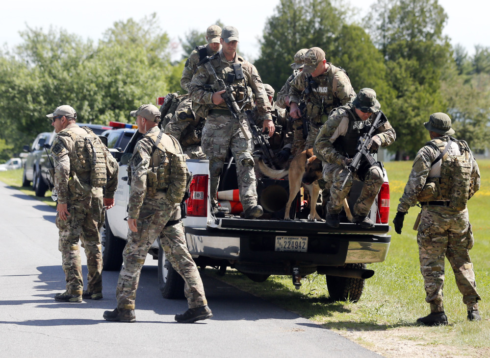 The Associated Press Law enforcement officers get off a truck as they return to their vehicles after searching a wooded area on Sunday in Schuyler Falls, N.Y.