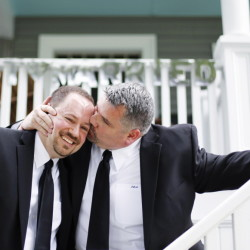 Jay Norris gives Doug Fillmore a kiss under the Just Married sign their neighhbors put up at their Eastern Promenade home in Portland. The couple were married in a small ceremony at the Cathedral Church of St. Luke.
