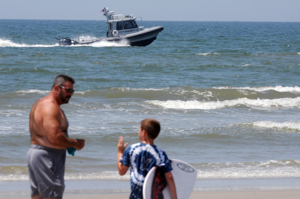 Jack Cross, 9, watches as a boat patrols the coastline near Ocean Crest Pier in Oak Island, N.C., on Monday, a day after two young people lost limbs in separate shark attacks in the town.