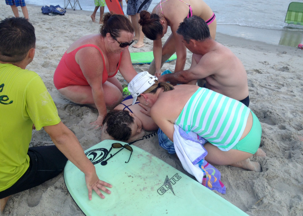 People assist a girl after she was attacked by a shark in Oak Island, N.C., on Sunday.