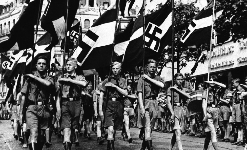 Boys march beneath Nazi standards in Berlin in 1936. Anti-Semitic propaganda had a lifelong effect on German children schooled during the Nazi period, leaving them far more likely to hold racist views than those born earlier and later.