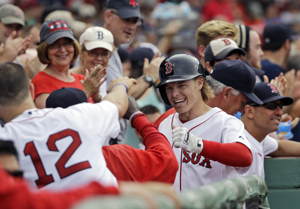 Boston's Brock Holt celebrates in the dugout after hitting a solo home run in the seventh inning of Tuesday's game against the Atlanta Braves. Holt later tripled to complete the cycle.