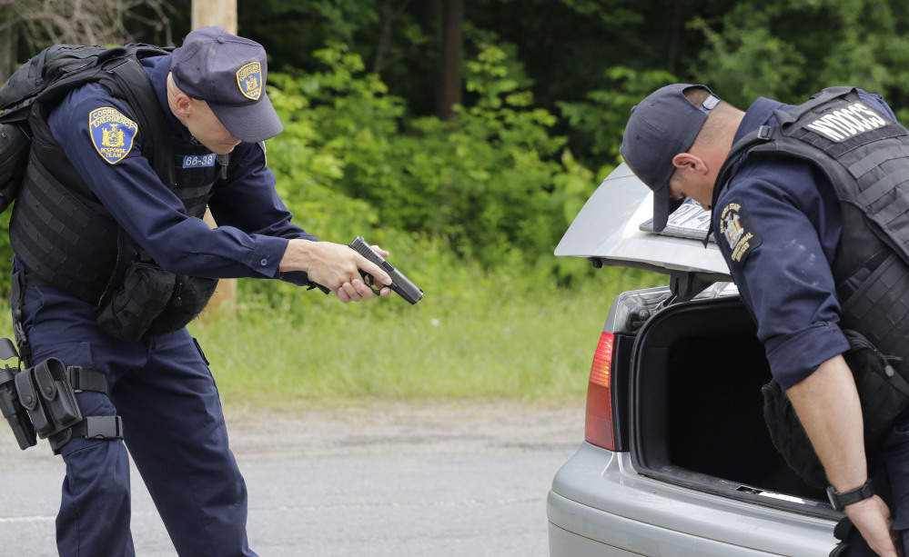 Guns drawn, officers with the New York State Department of Corrections inspect a vehicle Tuesday at a roadblock in Dannemora, N.Y.