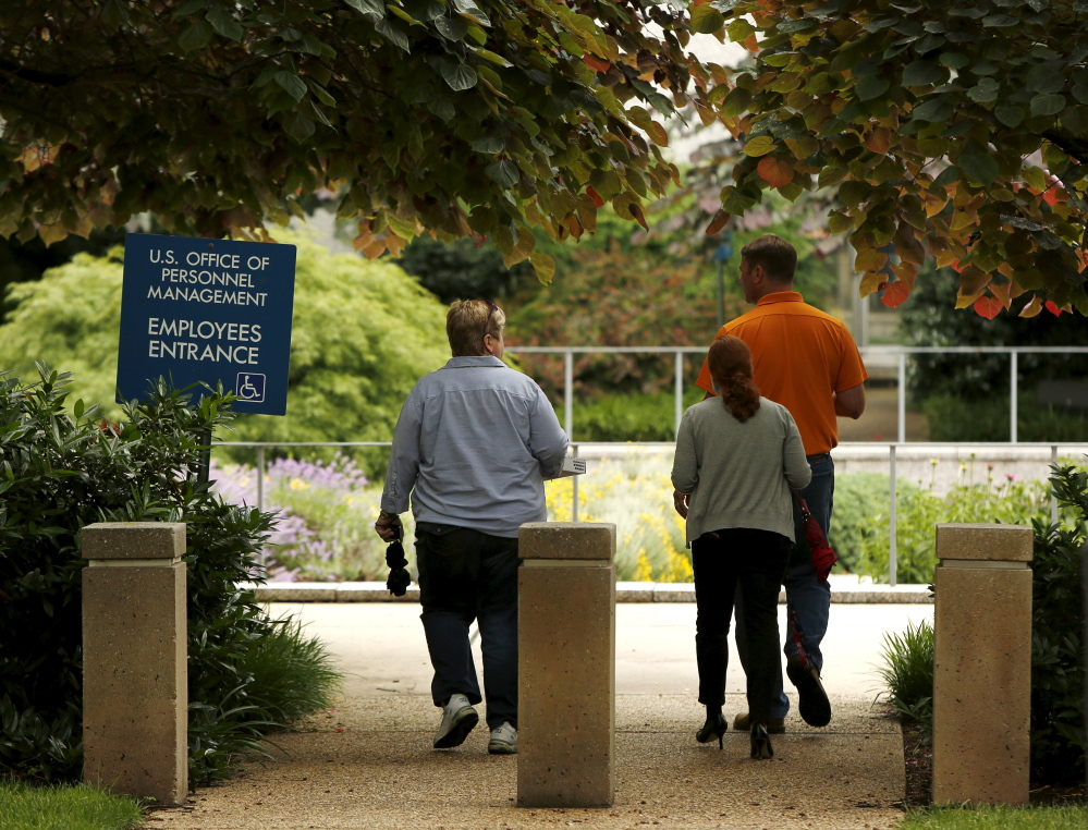 Employees of the U.S. Office of Personnel Management return to their building during the lunch hour in Washington last week.