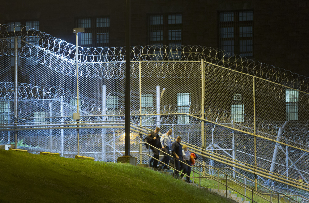Corrections officers walk next to a fence covered in razor wire as they leave work at the Clinton Correctional Facility, Monday, in Dannemora, N.Y.