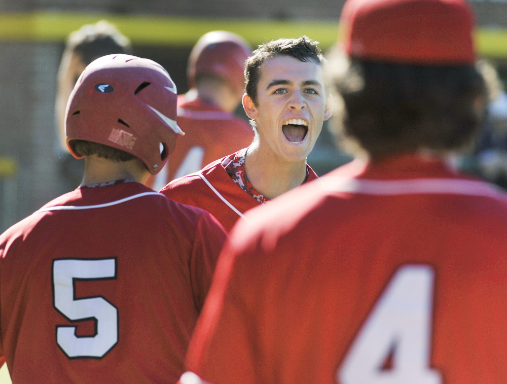 South Portland's Henry Curran is met by teammates after scoring what proved to be the winning run in the seventh inning Wednesday in the Western Class A baseball final at Standish. The Red Riots won, 2-1.